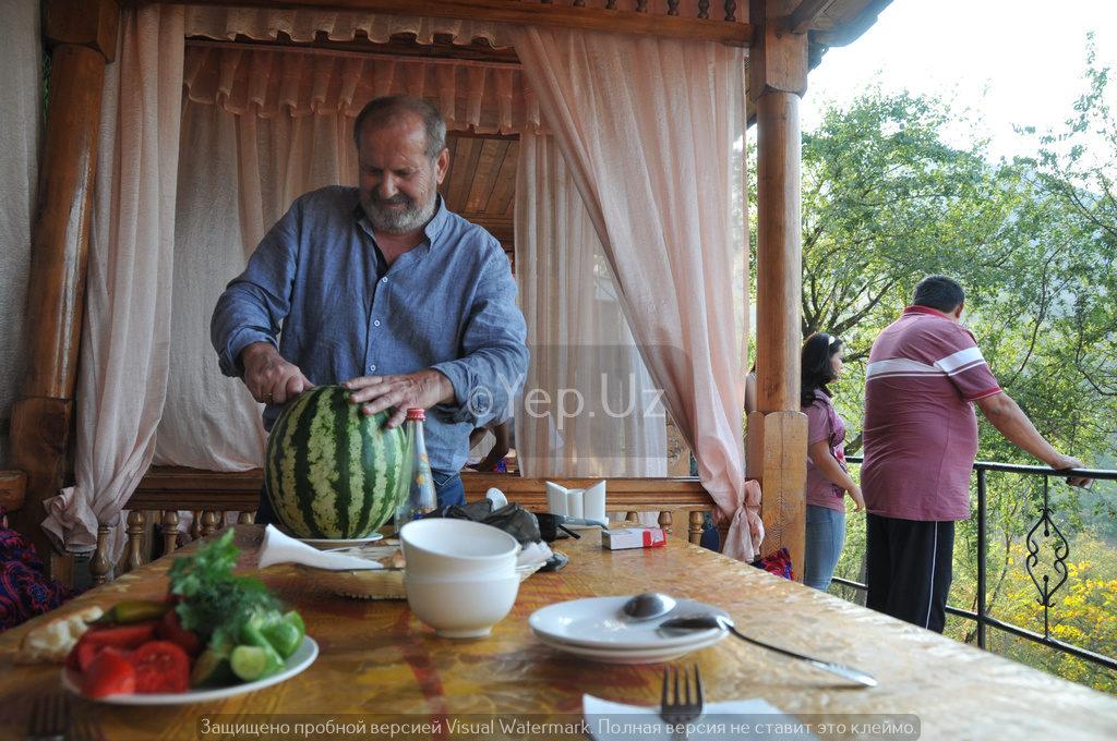 Владимир разрезает арбуз в одном из многочисленных кафе над Чарваком