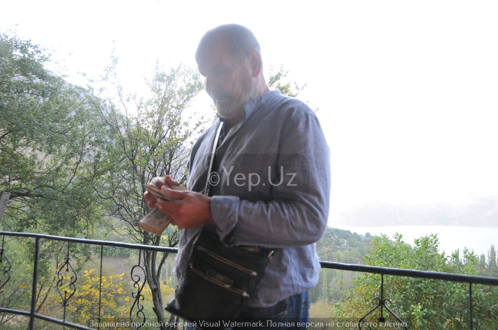 Владимир считает деньги, чтобы рассчитаься за обед в кафе над Чарваком