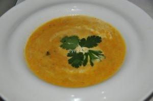 Суп-пюре из моркови и лука со сливками разлит по таелкам и украшан зеленью