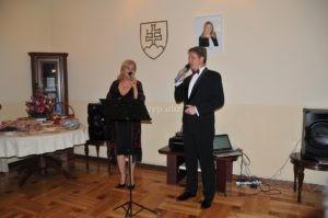 Моника Станиславова и Юрай Хавай поют для гостей словацкого посла в Ташкенте, на стене портрет президента Словакии Зузаны Чапутовой